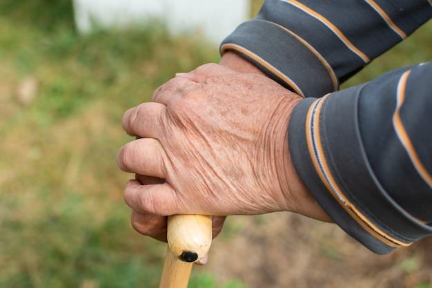 Ältere frau ruht auf einem hölzernen gehstock