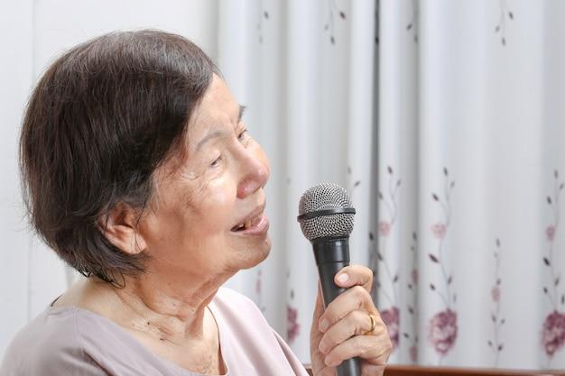 Ältere frau singen zu hause ein lied am mikrofon.