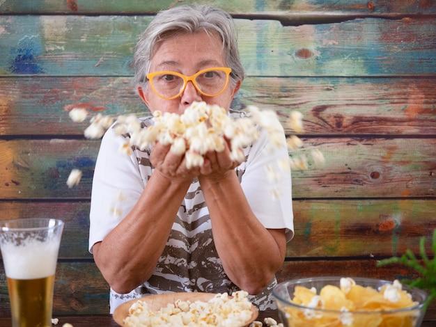 Ältere frau sitzt an einem holztisch mit bier und vorspeise, die auf popcorn in ihren händen bläst. ältere menschen, die spaß haben
