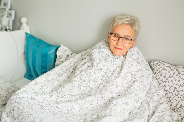 Ältere frau sitzt auf einem bett in einer decke