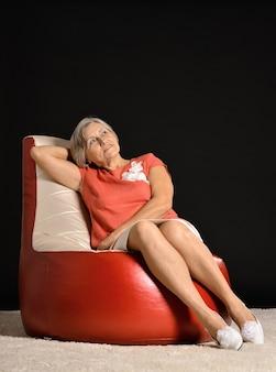 Ältere frau sitzt auf sessel im dunklen studio