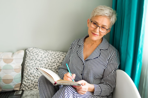 Ältere frau sitzt im schlafanzug auf dem bett