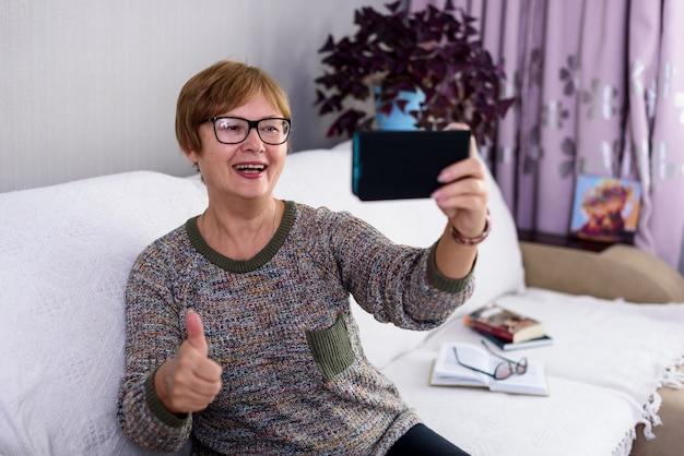 Ältere frau spricht von zu hause aus auf video und sagt, dass alles gut wird.
