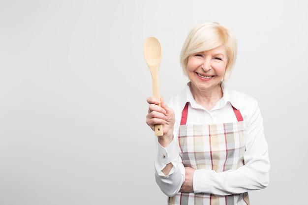 Ältere frau stehend und einen löffel haltend. sie ist eine gute hausfrau. sie kocht gerne leckeres essen.