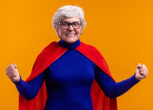Ältere frau superheld mit brille mit rotem umhang, der die kamera glücklich und aufgeregt mit geballten fäusten über orange anschaut