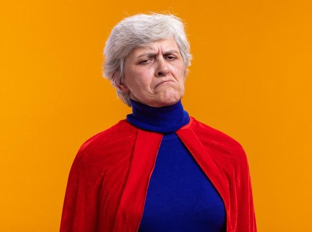 Ältere frau superheld mit rotem umhang, der die kamera anschaut und einen schiefen mund mit enttäuschtem ausdruck über orange macht