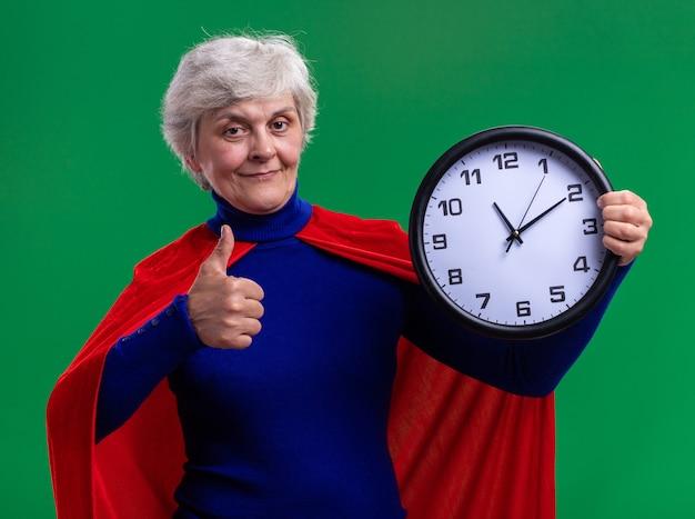 Ältere frau superheld mit rotem umhang, der die wanduhr hält und in die kamera schaut, lächelt zuversichtlich und zeigt daumen hoch