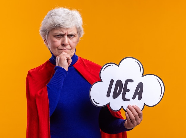 Ältere frau superheld mit rotem umhang, der ein sprechblasenschild mit wortidee hält und die kamera mit nachdenklichem gesichtsausdruck betrachtet, der über orangefarbenen hintergrund denkt