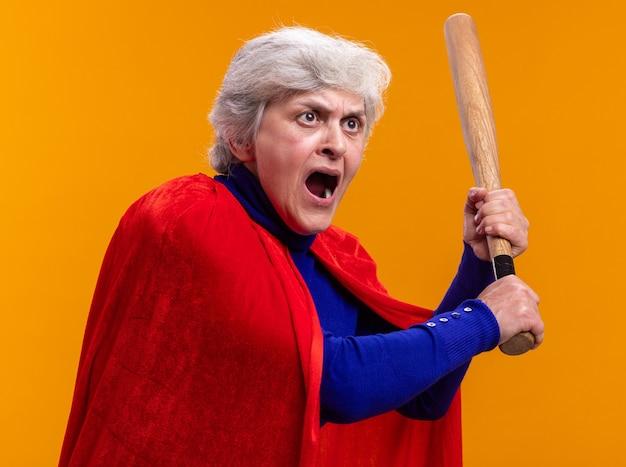 Ältere frau superheld mit rotem umhang hält baseballschläger schreien wütend und aufgeregt