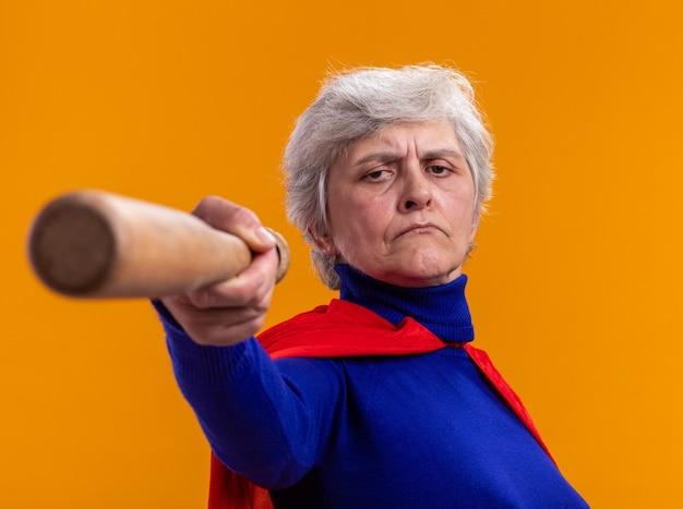 Ältere frau superheld mit rotem umhang mit baseballschläger auf kamera zeigend mit ernstem gesicht über orange stehend looking