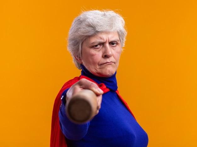 Ältere frau superheld mit rotem umhang mit baseballschläger auf kamera zeigend
