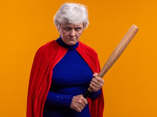 Ältere frau superheld mit rotem umhang mit baseballschläger und blick in die kamera mit stirnrunzelndem gesicht über orangefarbenem hintergrund