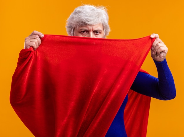 Ältere frau superheld mit rotem umhang mit blick auf die kamera, die das gesicht mit dem umhang bedeckt, der selbstbewusst auf orangefarbenem hintergrund steht