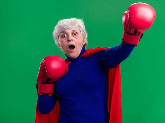 Ältere frau superheld mit rotem umhang mit boxhandschuhen und blick in die kamera verängstigt und besorgt über grünem hintergrund stehend
