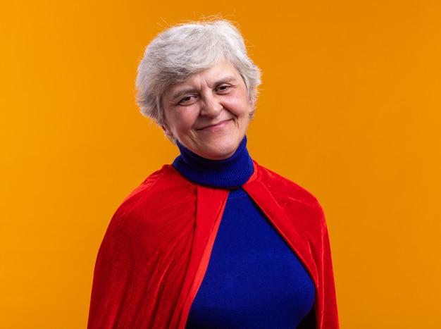 Ältere frau superheldin mit rotem umhang, die glücklich und positiv in die kamera schaut und fröhlich über orange lächelt