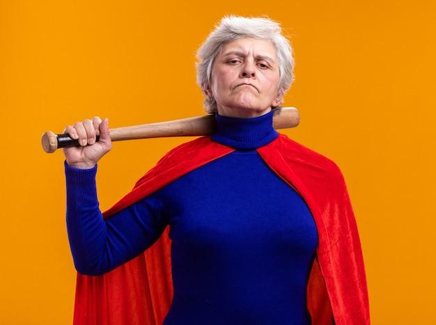 Ältere frau superheldin mit rotem umhang mit baseballschläger und blick in die kamera mit ernstem gesicht über orange