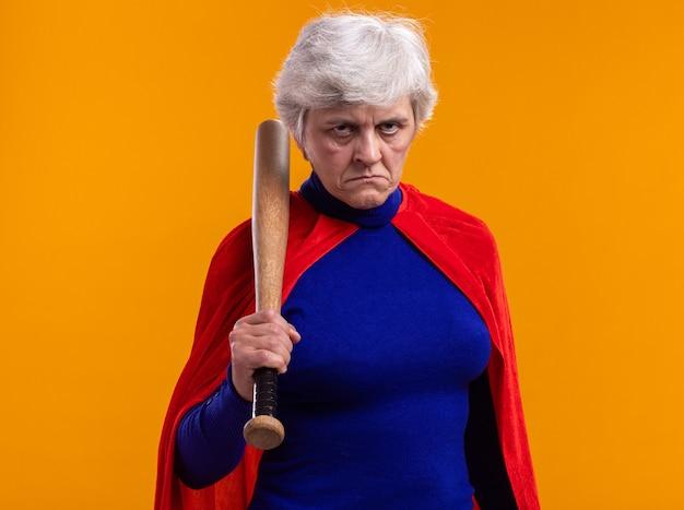 Ältere frau superheldin mit rotem umhang mit baseballschläger und blick in die kamera mit ernstem gesicht über orangefarbenem hintergrund