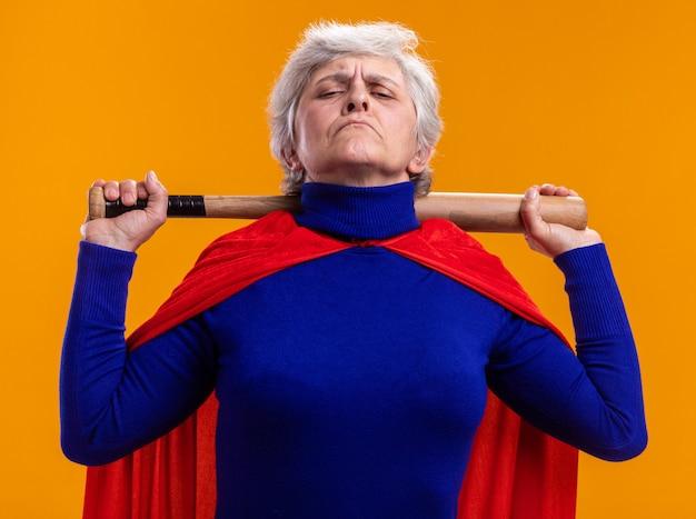 Ältere frau superheldin mit rotem umhang mit baseballschläger und blick in die kamera mit ernstem, selbstbewusstem ausdruck auf orangefarbenem hintergrund