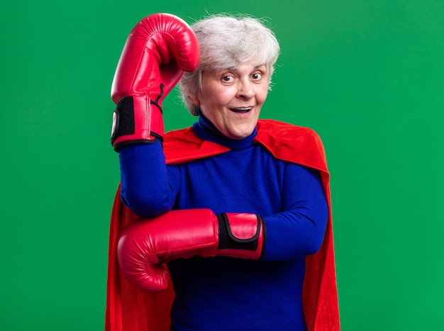 Ältere frau superheldin mit rotem umhang mit boxhandschuhen, die glücklich und überrascht in die kamera schaut, die über grünem hintergrund steht