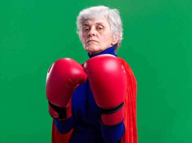 Ältere frau superheldin mit rotem umhang mit boxhandschuhen und blick in die kamera mit ernstem, selbstbewusstem ausdruck, der bereit ist, über grünem hintergrund zu kämpfen