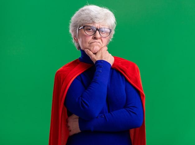 Ältere frau superheldin mit rotem umhang und brille, die kamera mit skeptischem ausdruck auf grünem hintergrund betrachtet