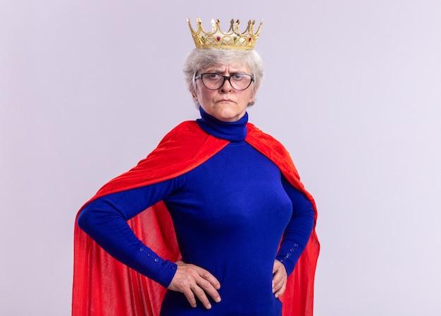 Ältere frau superheldin mit rotem umhang und brille mit krone auf dem kopf, die kamera mit ernstem gesicht mit armen an der hüfte auf weißem hintergrund betrachtet