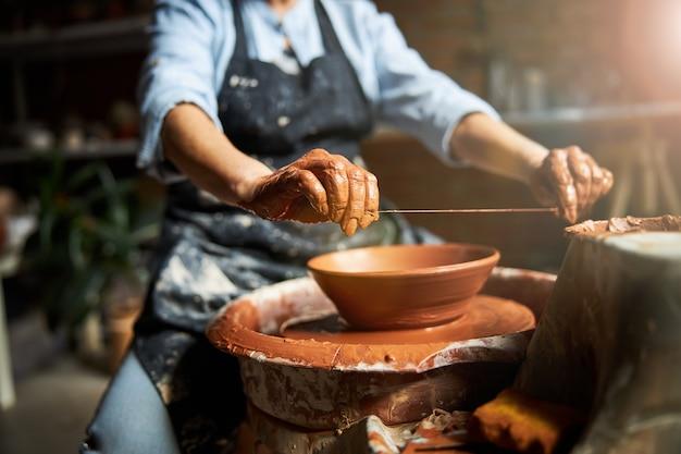 Ältere frau töpfer unter verwendung drahtdrahtschneider während der arbeit an töpferscheibe
