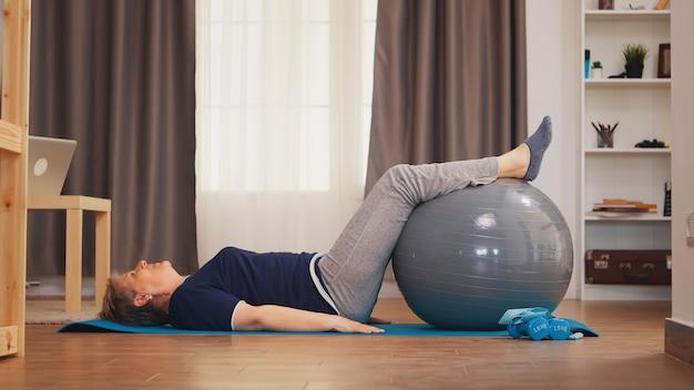 Ältere frau trainiert bauchmuskeln auf dem schweizer ball im wohnzimmer. gesunder lebensstil rentner des alten menschen, der zu hause sport- und wellnesstraining zuhause lebt