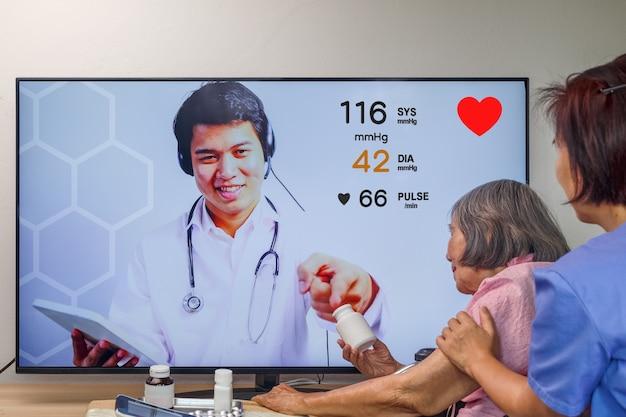 Ältere frau trifft einen online-arzt mit einem gesundheitsberater.