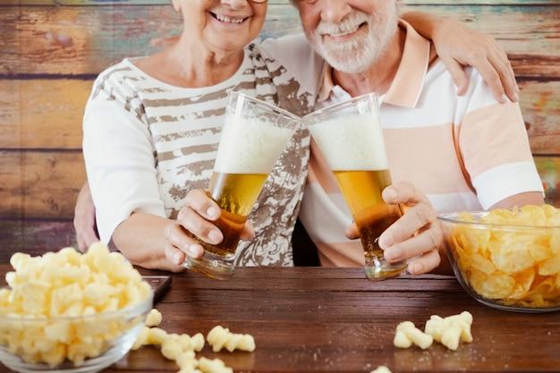 Ältere frau und ehemann, die mit zwei gläsern bier und kartoffelchips anstoßen, während sie an einem holztisch in der kneipe sitzen. glückliches entspanntes rentnerehepaar