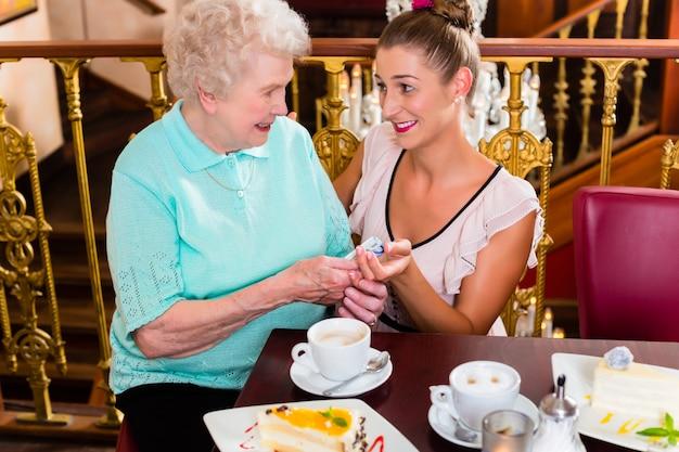 Ältere frau und enkelin am kaffee im café