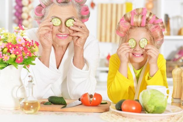 Ältere frau und enkelin an der küche mit gemüse