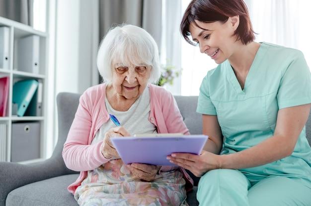 Ältere frau und krankenschwester unterschreiben dokumente zu hause. mädchen im gesundheitswesen kümmert sich um die ältere weibliche person im haus