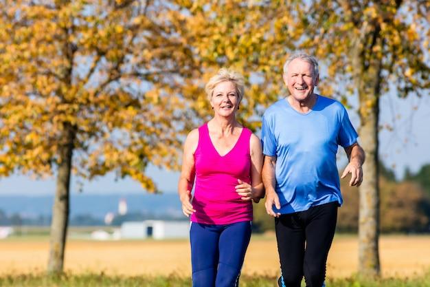 Ältere frau und mann, die eignungsübungen tuend läuft