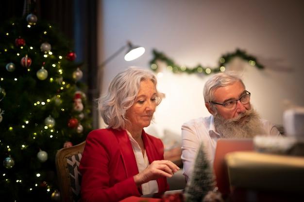 Ältere frau und mann, die weihnachten feiert