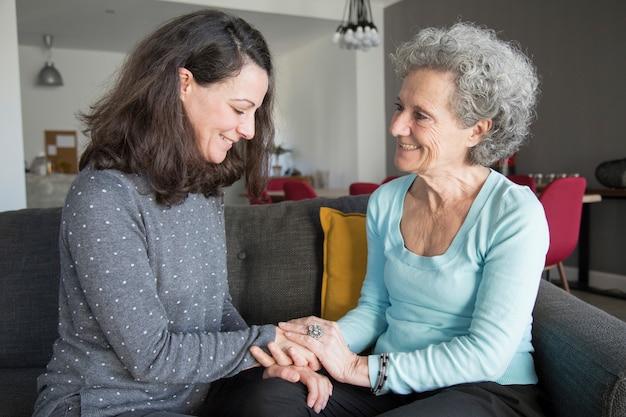 Ältere frau und tochter, die zu hause plaudert