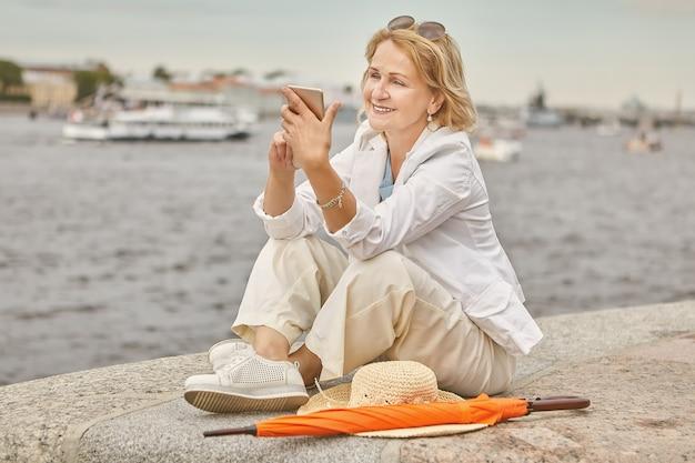 Ältere frau ungefähr 60 jahre alt sitzt in der nähe des flusses in lässigem und elegantem stoff mit smartphone in händen in sankt petersburg.