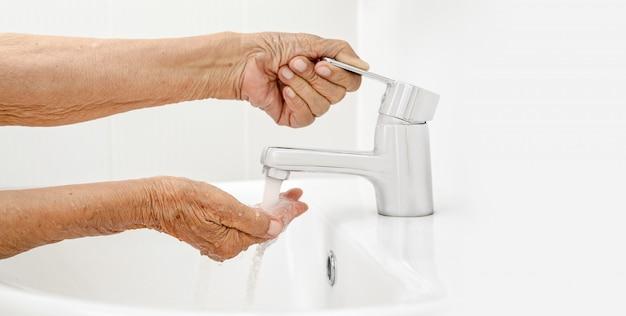 Ältere frau wäscht hand im badezimmer