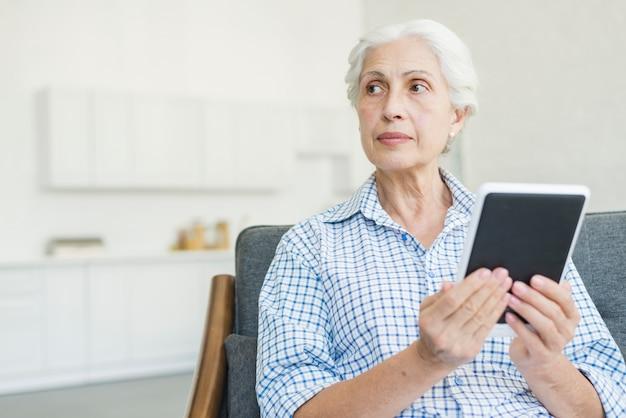 Ältere frau, welche die digitale tablette weg schaut hält