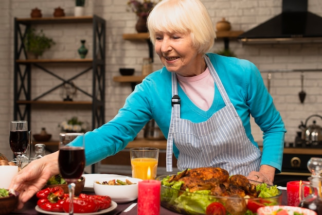 Ältere frau, welche die erntedankmahlzeit vorbereitet