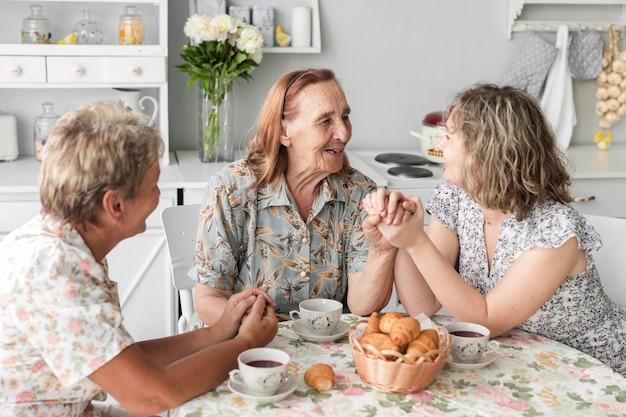 Ältere frau, welche die hand ihrer tochter und der großartigen tochter während des frühstücks hält