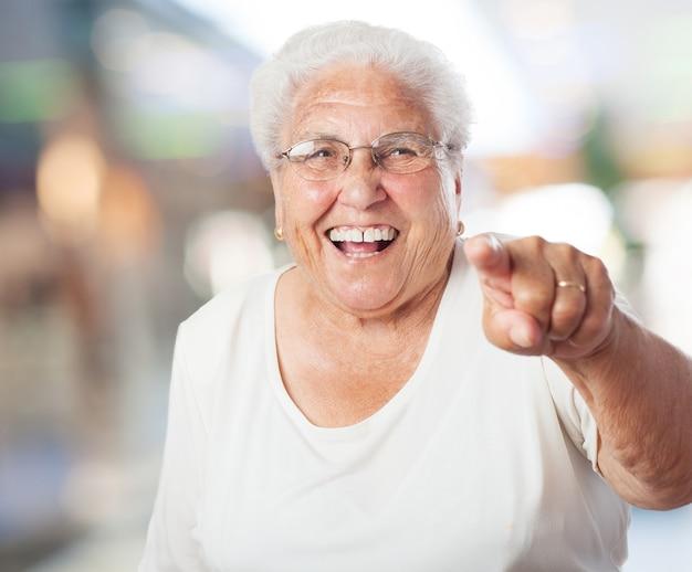 Ältere frau zeigen und lachen