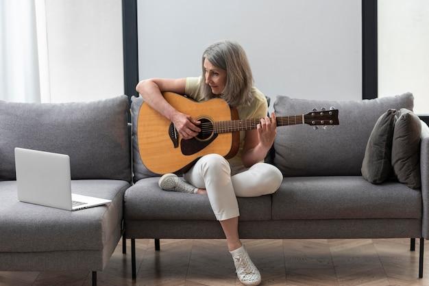 Ältere frau zu hause auf der couch mit laptop für gitarrenunterricht