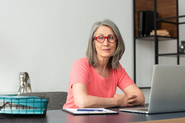 Ältere frau zu hause, die am laptop studiert