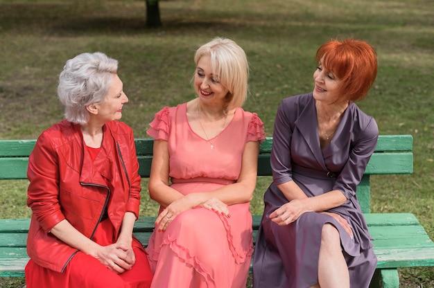 Ältere frauen, die auf einer bank sitzen
