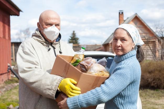 Ältere frauen, die aufgrund des coronavirus covid19 einem hohen risiko ausgesetzt sind, erhalten mahlzeiten oder lebensmittel zu sich nach hause geliefert
