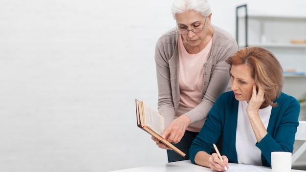 Ältere frauen, die ein buch untersuchen