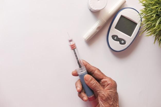 Ältere frauen, die insulinpens mit kopierraum halten, von oben nach unten.