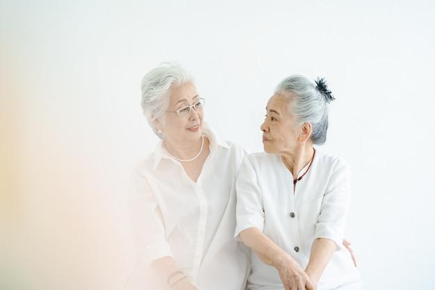 Ältere frauen, die mit einem lächeln im hellen raum sprechen
