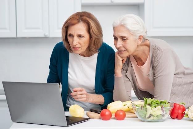 Ältere frauen, die nach dem kochen von rezepten suchen
